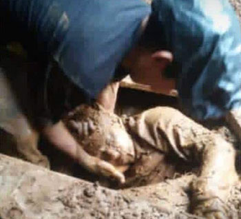 A child's body is recovered from the mud.