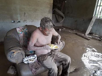 A boy eats in his home after Eta.