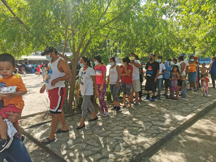 People wait in line for food at a Kids Ark International relief location in Honduras